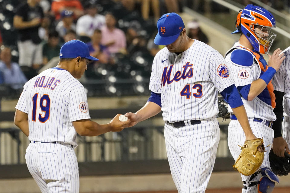 New York Mets starting pitcher Jerad Eickhoff (43) hands the ball to manager Luis Rojas (19) after being removed during the fourth inning of the team's baseball game against the Atlanta Braves, Tuesday, July 27, 2021, in New York. (AP Photo/Mary Altaffer)