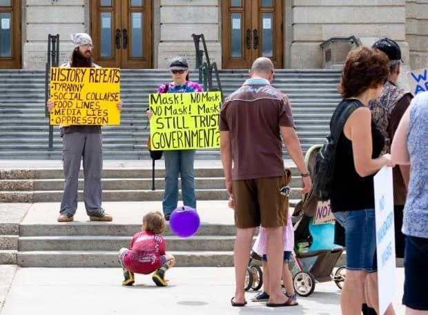Participants are seen at an anti-mask rally in Regina in July. Health policy experts say this extremely vocal minority is the cause of the Saskatchewan government's inaction on COVID-19. (Bryan Eneas/CBC - image credit)