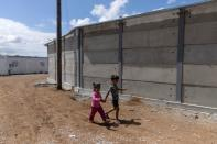 FILE PHOTO: Children walk next to a newly built concrete wall inside the Ritsona camp for refugees and migrants