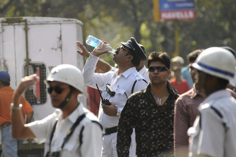 """<span class=""""caption"""">A thirsty traffic police constable drinking water on a hot day Kolkata.</span>"""