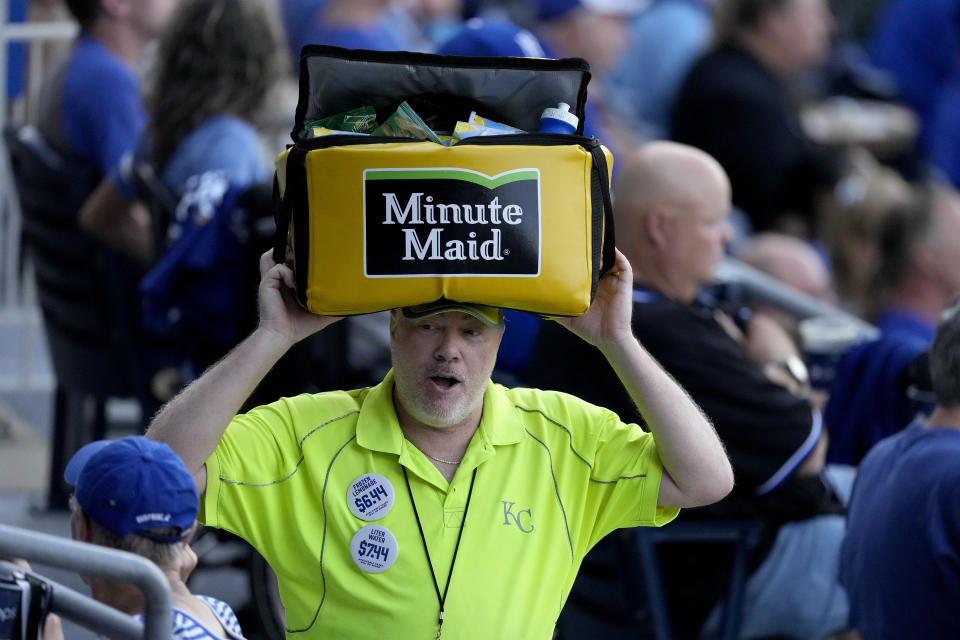 A vendor works the crowd during a baseball game between the Kansas City Royals and the Cincinnati Reds Tuesday, July 6, 2021, in Kansas City, Mo. With baseball fans back in the stands and concessions being sold, ballpark employees have had a chance to return after the pandemic hit many of them hard. (AP Photo/Charlie Riedel)