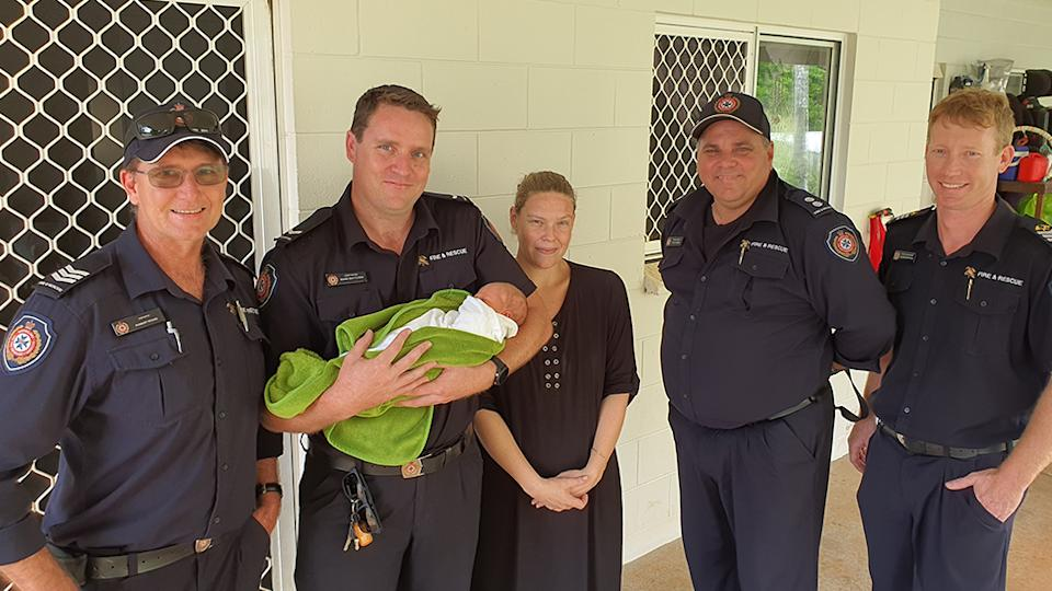 The firefighter crew pose with the baby during their return visit.
