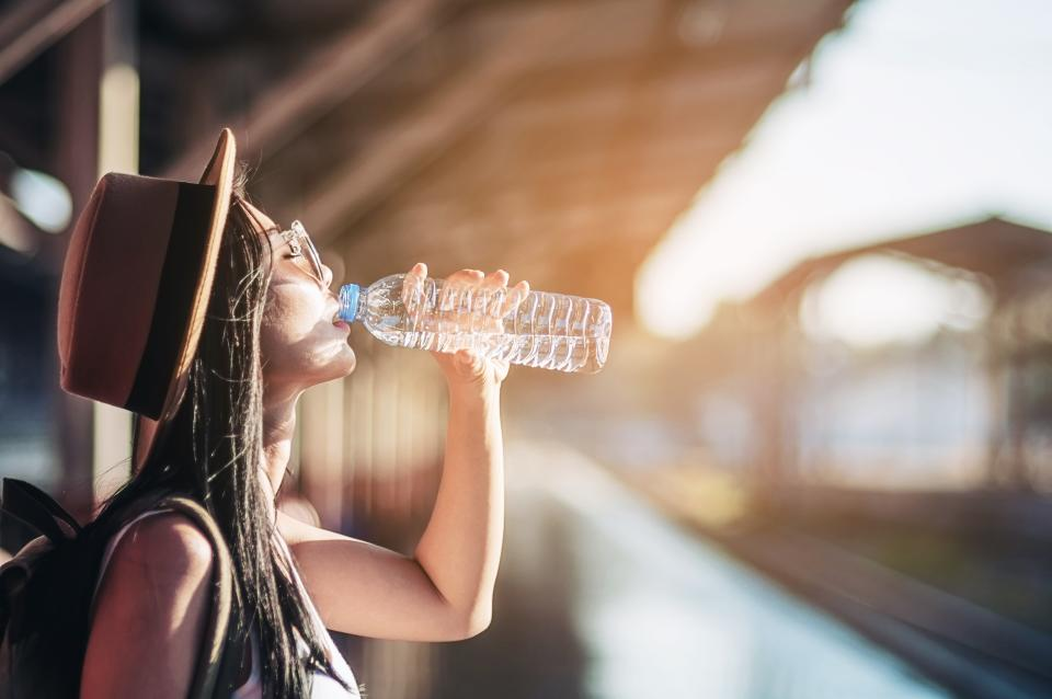 Woman Drinking Water From Bottle At Railroad Station Platform