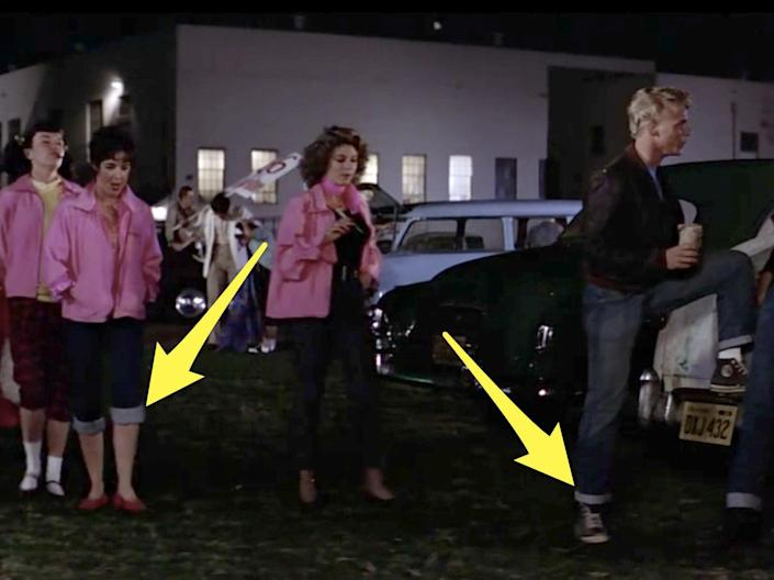 the pink ladies and t-birds meeting outside with arrows pointing at their cuffed jeans