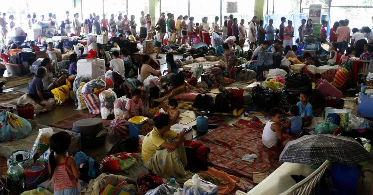 Residents take shelter at a basketball covered court after they were evacuated at the height of Typhoon Kalmaegi in Marikina, Metro Manila September 15, 2014. A strong typhoon slammed into the rice-producing Philippine northern region on Sunday, cutting power and communications lines and forcing people to flee to higher ground, national disaster agency officials said. REUTERS/Erik De Castro (PHILIPPINES - Tags: SOCIETY DISASTER ENVIRONMENT)