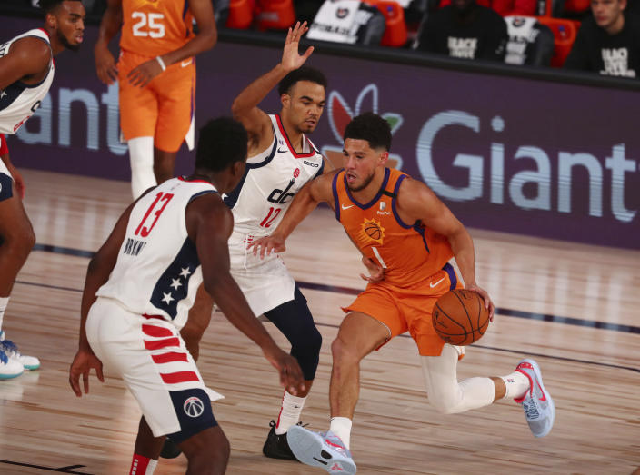 Phoenix Suns guard Devin Booker (1) drives to the basket against Washington Wizards guard Jerome Robinson (12) in the first half an NBA basketball game in Lake Buena Vista, Fla., Friday, July 31, 2020. (Kim Klement/Pool Photo via AP)