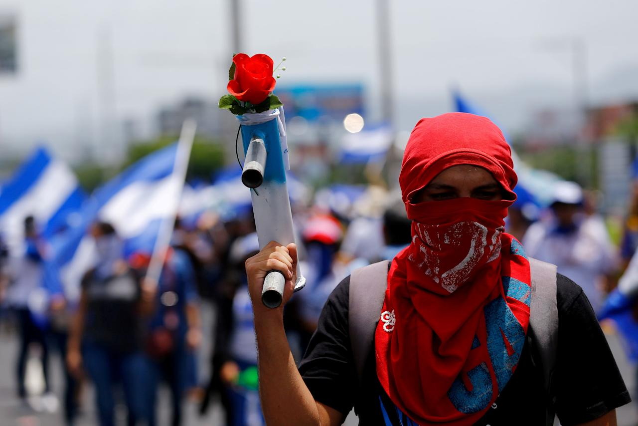A masked demonstrator holds a homemade mortar with a flower during a march to demand the release of the political prisoners arrested during recent protests against Nicaragua's President Daniel Ortega's government in Managua, Nicaragua July 21, 2018. REUTERS/Oswaldo Rivas      TPX IMAGES OF THE DAY