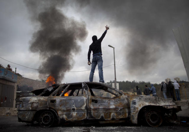 "<p>A Palestinian demonstrator stands on a burned-out car during clashes with Israeli troops following a demonstration to mark the 63rd anniversary of ""Nakba"" — Arabic for ""Catastrophe""— in the east Jerusalem neighborhood of Issawiyeh, May 15, 2011. (Photo: Oded Balilty/AP) </p>"