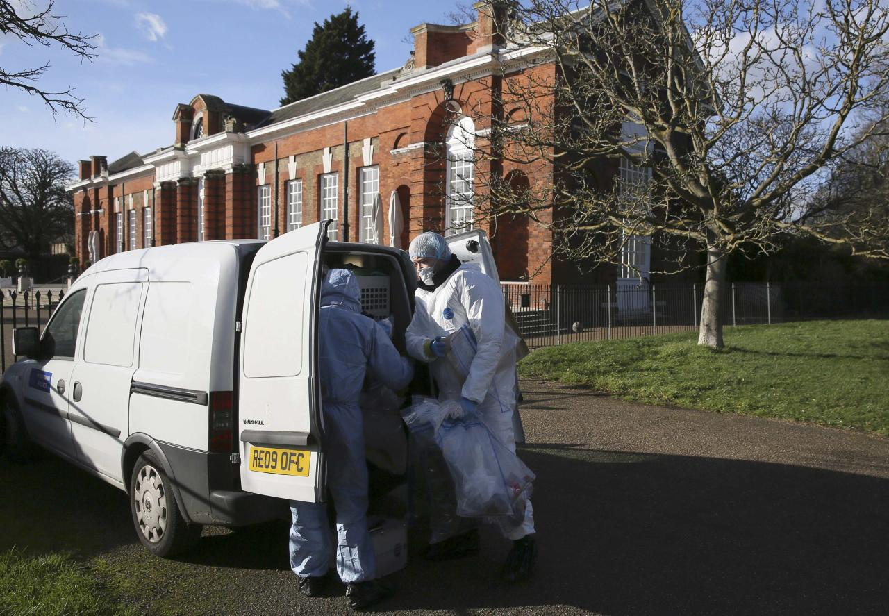 Forensic police officers put evidence into a van in an area near the grounds of Kensington Palace in London, Britain