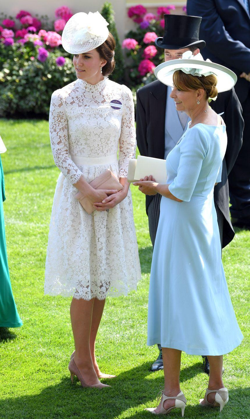 <p>The Duchess wore McQueen white lace, reminiscent of her wedding gown, to 2017's Royal Ascot horse race. Here, she chats with her mother, Carole Middleton. </p>