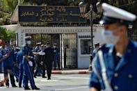 Algerian security forces stand guard outside the El-Alia cemetary where Abdelaziz Bouteflika, the North African country's longest-serving president, is set to be buried in the capital Algiers on September 19, 2021 (AFP/RYAD KRAMDI)