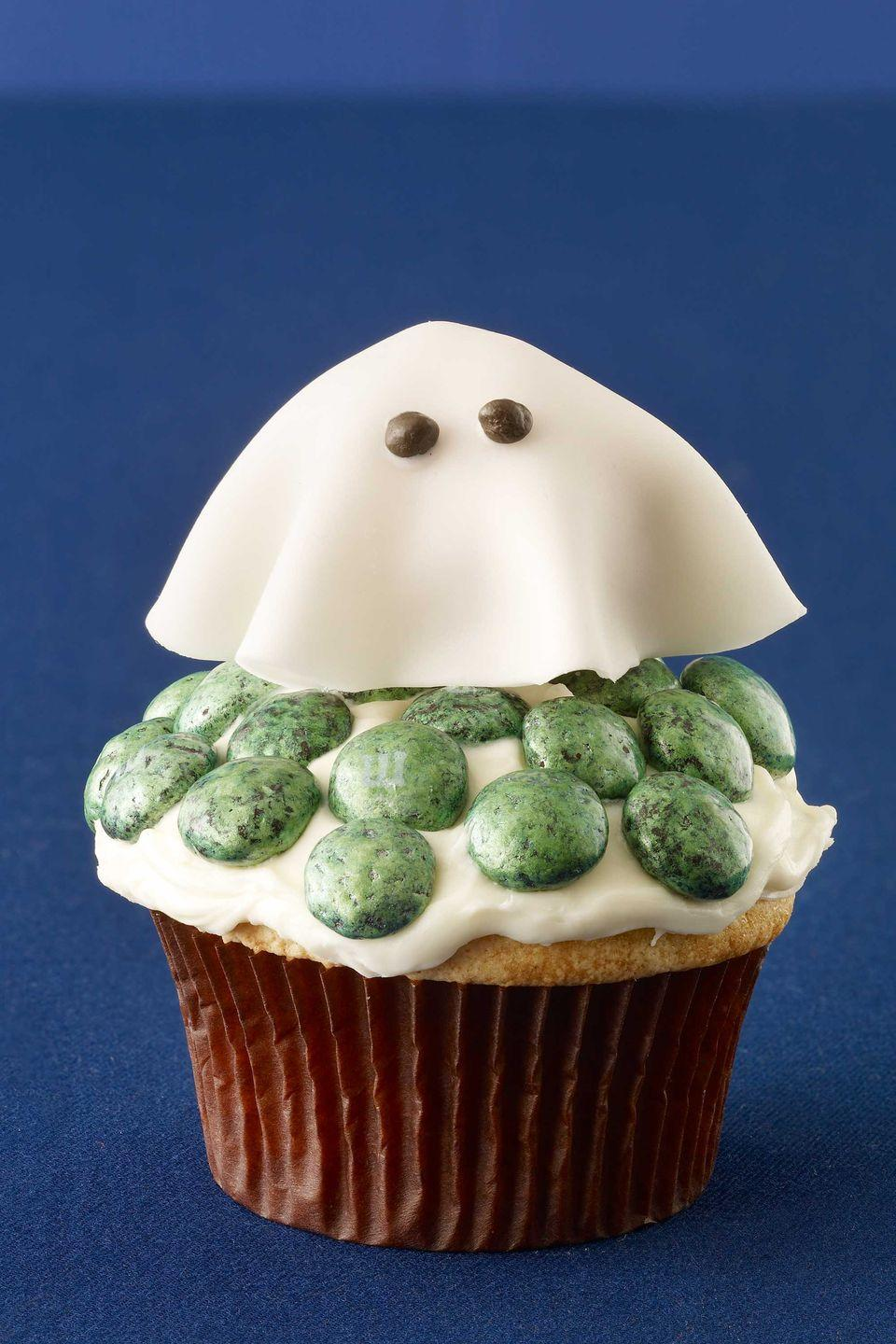"""<p>There's nothing sinister about these treats — just enticing sweetness, with a fondant-covered doughnut-hole ghost floating on a bed of vanilla frosting and dotted with mint chocolate M&M's.</p><p><a href=""""https://www.womansday.com/food-recipes/food-drinks/recipes/a11455/friendly-ghost-cupcake-recipe-122729/"""" rel=""""nofollow noopener"""" target=""""_blank"""" data-ylk=""""slk:Get the Friendly Ghost Cupcake recipe."""" class=""""link rapid-noclick-resp""""><em>Get the Friendly Ghost Cupcake recipe.</em></a></p>"""