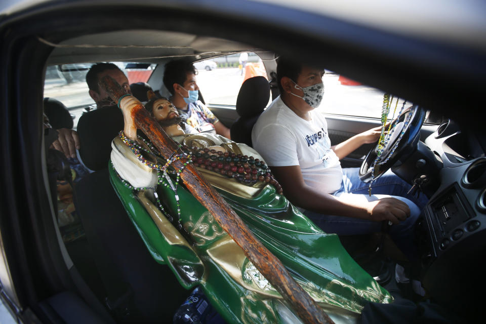 A Saint Jude statue is transported in the passenger seat of a car during the annual pilgrimage honoring Jude, the patron saint of lost causes, in Mexico City, Wednesday, Oct. 28, 2020. Thousands of Mexicans did not miss this year to mark St. Jude's feast day, but the pandemic caused Masses to be canceled and the rivers of people of other years outside the San Hipolito Catholic church were replaced by orderly lines of masked worshipers waiting their turn for a blessing. (AP Photo/Marco Ugarte)