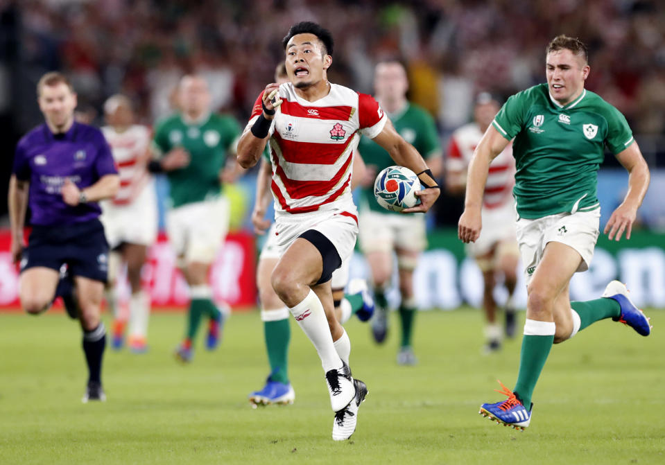 Japan's Kenki Fukuoka, center, runs past Ireland's defense during the Rugby World Cup Pool A game at Shizuoka Stadium Ecopa between Japan and Ireland in Shizuoka, Japan, Saturday, Sept. 28, 2019. (Naoya Osato/Kyodo News via AP)