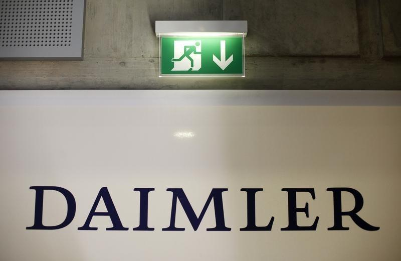 A emergency exit sign is pictured above a logo of German car manufacturer Daimler AG, before the annual news conference in Stuttgart