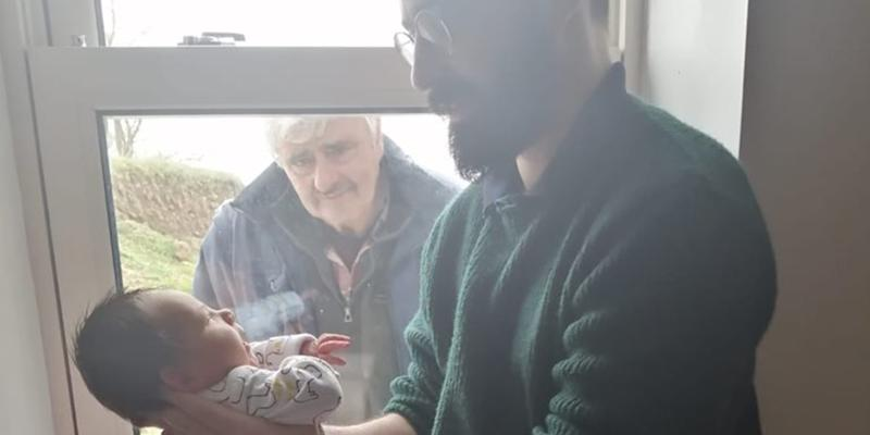 Grandfather meets newborn grandson through a window in heartbreaking photo