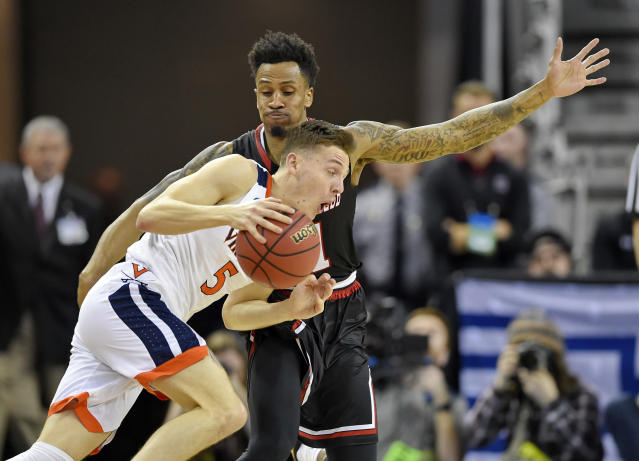 Virginia's Kyle Guy (5) drives against Gardner-Webb's David Efianayi (11) during a first-round game in the NCAA men's college basketball tournament in Columbia, S.C., Friday, March 22, 2019. (AP Photo/Richard Shiro)