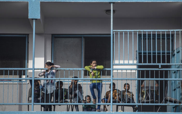 Palestinians take shelter provided by the U.N. at a school after fleeing their homes from the overnight Israeli heavy missile strikes on their neighborhoods in the outskirts of Gaza City, Friday, May 14, 2021. (AP Photo/Khalil Hamra)