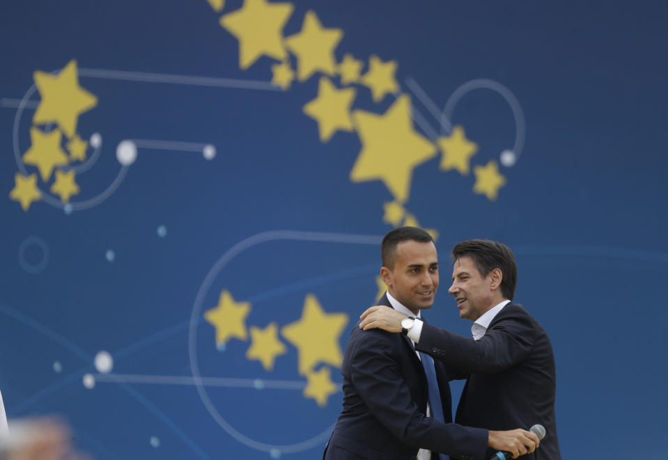 FILE - In this Sunday, Oct. 21, 2018 file photo, Vice Premier Luigi Di Maio, right, and Italian Premier Giuseppe Conte Hugh each other during a Five Stars Movement rally at Rome's Circus Maximus. When Giuseppe Conte exited the premier's office, palace employees warmly applauded in him appreciation. But that's hardly likely to be Conte's last hurrah in politics. Just a few hours after the handover-ceremony to transfer power to Mario Draghi, the former European Central Bank chief now tasked with leading Italy in the pandemic, Conte dashed off a thank-you note to citizens that sounded more like an ''arrivederci″ (see you again) then a retreat from the political world he was unexpectedly propelled into in 2018. (AP Photo/Gregorio Borgia, File)