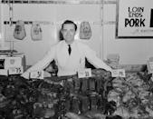 <p>A smiling butcher stands at a meat counter displaying cuts ranging from 19 cents to 31 cents per pound.</p>
