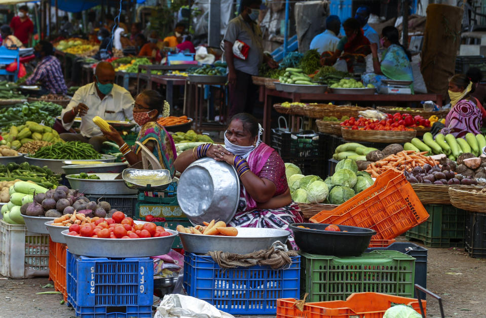 Indian vendors wearing face masks as a precaution against coronavirus wait for customers at a vegetable market in Hyderabad, India, Thursday, June 24, 2021. (AP Photo/Mahesh Kumar A.)
