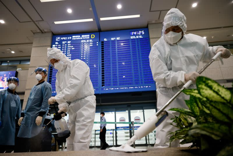 Workers wearing protective gear disinfect an arrival gate as an electronic board shows arrivals' information at the Incheon International Airport, in Incheon
