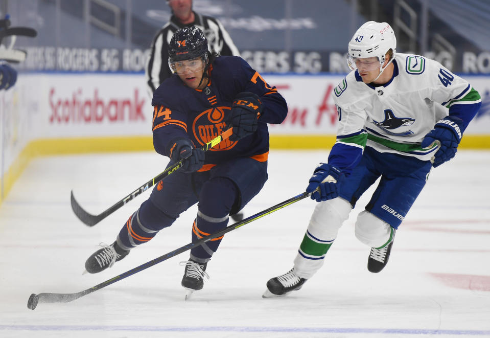 Edmonton Oilers' Ethan Bear (74) and Vancouver Canucks' Elias Pettersson (40) vie for the puck during the second period of an NHL hockey game Wednesday, Jan. 13, 2021, in Edmonton, Alberta. (Dale MacMillan/The Canadian Press via AP)