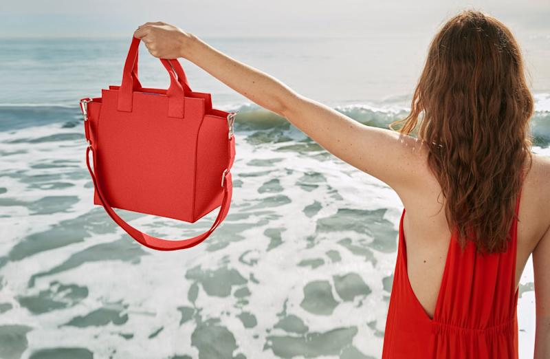 Woman on the beach holds up Rothy's new Handbag in poppy red.