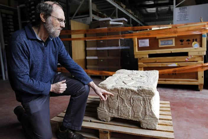 Professor Gideon Avni of the Israel Antiquities Authority displays the original Magdala Stone which was discovered in a Galilean synagogue dating to the Second Temple period (50 BC-100 AD) (AFP Photo/MENAHEM KAHANA)