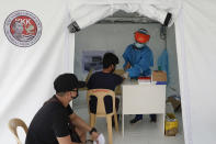 Health workers perform a rapid test on a man at a parking lot that has been converted into an extension of the Gat Andres Bonifacio Memorial Medical Center in Manila, Philippines on Monday, Aug. 3, 2020. Philippine President Rodrigo Duterte is reimposing a moderate lockdown in the capital and outlying provinces after medical groups appealed for the move as coronavirus infections surge alarmingly. (AP Photo/Aaron Favila)