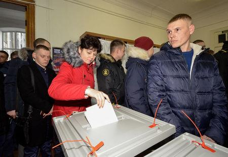 A woman casts her ballot during the presidential election at a polling station in the far eastern city of Vladivostok, Russia March 18, 2018.  REUTERS/Yuri Maltsev