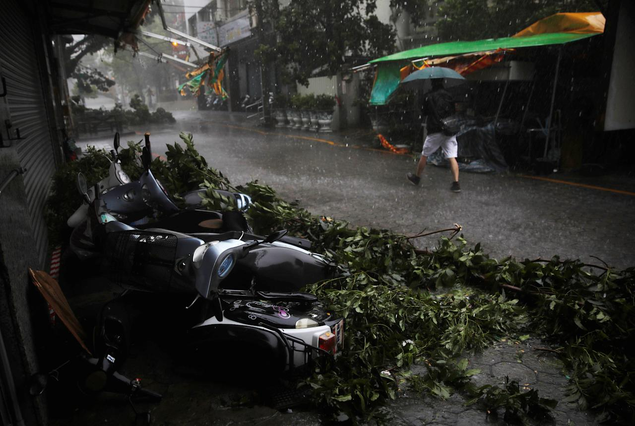 A man walks past motorcycles damaged by Typhoon Megi in Hualien, eastern Taiwan September 27, 2016. REUTERS/Tyrone Siu     TPX IMAGES OF THE DAY