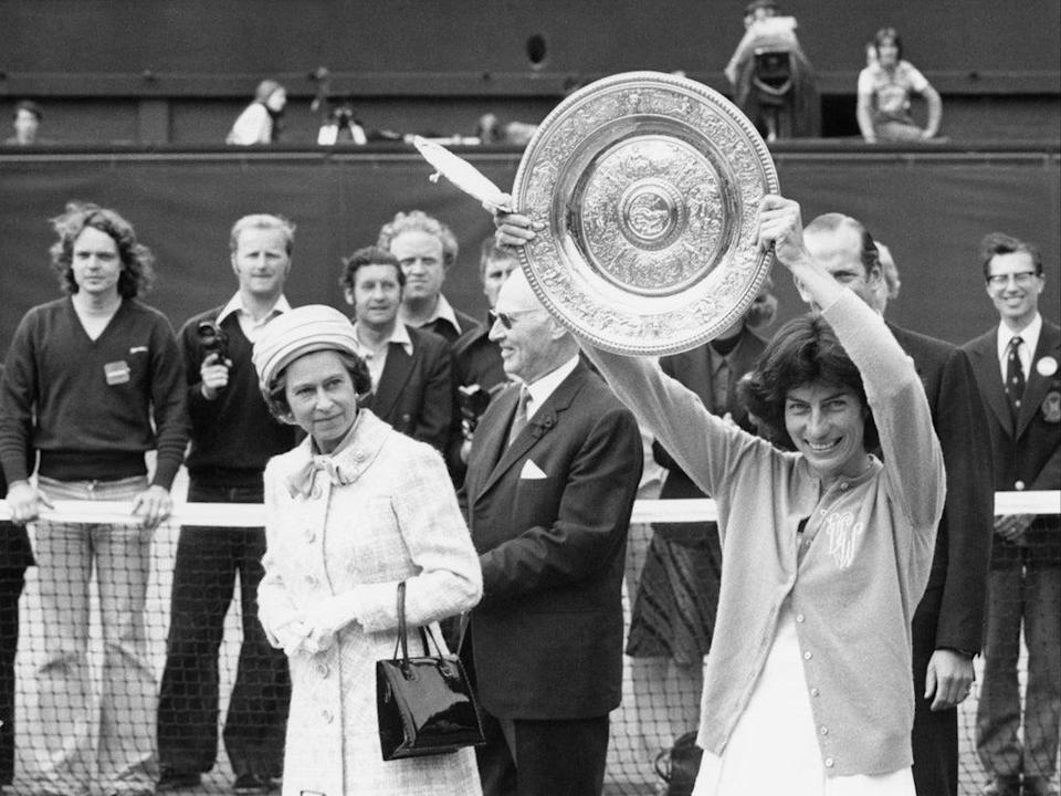 Queen Elizabeth II watches as Virginia Wade holds aloft the Wimbledon Women's Singles trophy to the crowd on Centre Court on 1 July 1977 (Mike Stephens/Central Press/Hulton Archive/Getty)