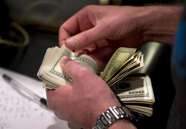 FILE PHOTO: A man counts out $100 bills as he makes a bet on Super Bowl XLVIII at the Las Vegas Hotel & Casino Superbook in Las Vegas, Nevada, U.S., January 23, 2014. REUTERS/Las Vegas Sun/Steve Marcus/File Photo