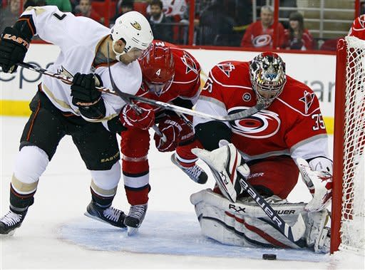 Carolina Hurricanes goalie Justin Peters (35) guards the post from a shot by Anaheim Ducks' Andrew Cogliano (7) with Hurricanes' Jamie McBain (4) during the first period of an NHL hockey game in Raleigh, N.C., Thursday, Feb. 23, 2012. (AP Photo/Karl B DeBlaker)