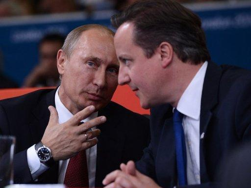 Russia's President Vladimir Putin (L) and British Prime Minister David Cameron (R) watch the judo