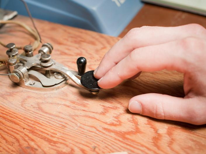 A man works a telegraph key at a desk. (Getty Images)
