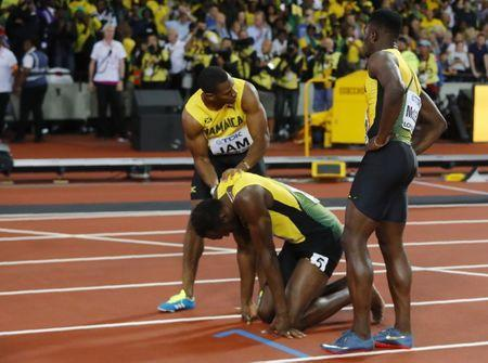 Athletics - World Athletics Championships - Men's 4x100 Metre Final - London Stadium, London, Britain – August 12, 2017. Usain Bolt of Jamaica reacts with Yohan Blake after sustaining an injury. REUTERS/Kai Pfaffenbach