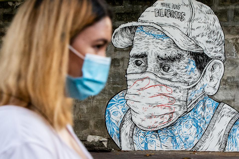 FILE PHOTO: A woman walks past a mural depicting a man whose mouth and nose are covered with a mask and a hand in Quezon City, Philippines on July 17, 2020. (Photo by Lisa Marie David/NurPhoto via Getty Images)