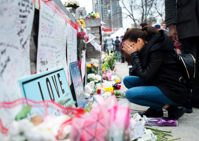 <p>A women fights back tears at a memorial along Yonge Street, Tuesday, April 24, 2018, in Toronto, the day after a driver drove a van down sidewalks, striking and killing numerous pedestrians in his path. (Photo: Nathan Denette/The Canadian Press via AP) </p>