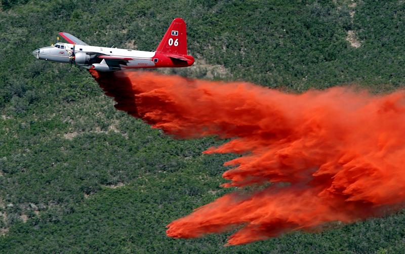 FILE - In this July 3, 2012 photo, an aircraft makes a drop on the Quail Fire above Alpine, Utah. The demise of a California company that built a device that sprays fire retardant from U.S. military C-130 cargo planes has some experts worried that a lack of spare parts and maintenance could create more problems for a program with a long record of success in fighting wildfires. Aero Union of Sacramento closed last year after the U.S. Forest Service canceled a contract worth a guaranteed minimum $14.5 million a year for six civilian air tankers, saying the company wasn't keeping up with inspections. (AP Photo/The Salt Lake Tribune, Steve Griffin)