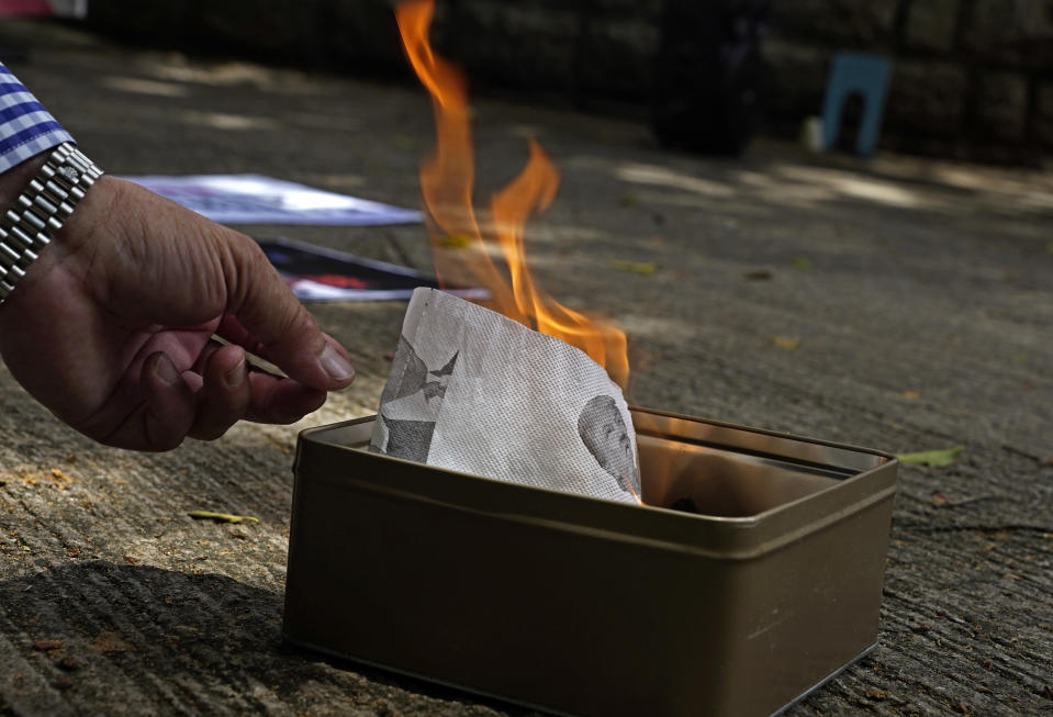 A pro-China supporter burns a picture of U.S. President Donald Trump during a protest against the U.S. sanctions outside the U.S. Consulate in Hong Kong Saturday, Aug. 8, 2020. The U.S. on Friday imposed sanctions on Hong Kong officials, including the pro-China leader of the government, accusing them of cooperating with Beijing's effort to undermine autonomy and crack down on freedom in the former British colony. (AP Photo/Vincent Yu)