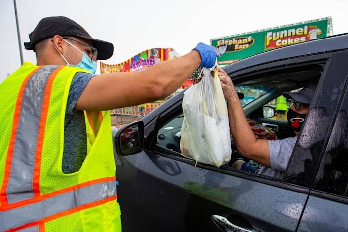 Food vendor employee Alejandro Pons, 18 delivers an order to the window of a driver during the Miami-Dade County Youth Fair food drive-through in Miami, Florida on Saturday, July 11, 2020.