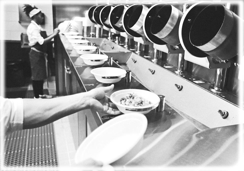 A worker lifts a lunch bowl off the production line at Spyce, a restaurant which uses a robotic cooking process, in Boston. (Photo: Charles Krupa/AP, digitally enhanced by Yahoo News)