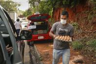 Midfielder Sergio Rojas of Club Sportivo Ameliano promotional division, sells carton of eggs from the back of his car, in Asuncion, Paraguay, Friday, Jan. 29, 2021. Because the championship was suspended due to the COVID-19 lockdown, Rojas, 28, a 10-year veteran of the league, now sells eggs and washes cars to survive after not being paid a salary for a year. (AP Photo/Jorge Saenz)