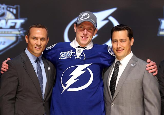 PITTSBURGH, PA - JUNE 22: Slater Koekkoek (C), tenth overall pick by the Tampa Bay Lightning, poses on stage with general manager Steve Yzerman (L) and team representatives during Round One of the 2012 NHL Entry Draft at Consol Energy Center on June 22, 2012 in Pittsburgh, Pennsylvania. (Photo by Bruce Bennett/Getty Images)