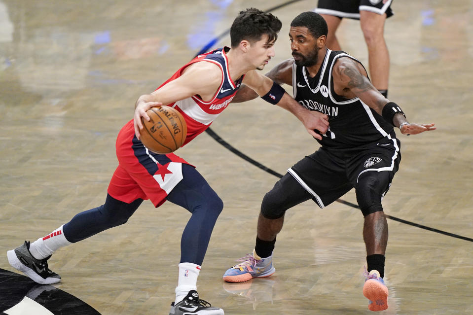 Brooklyn Nets guard Kyrie Irving (11) defends Washington Wizards rookie forward Deni Avdija (9) as Avdija drives toward the basket.