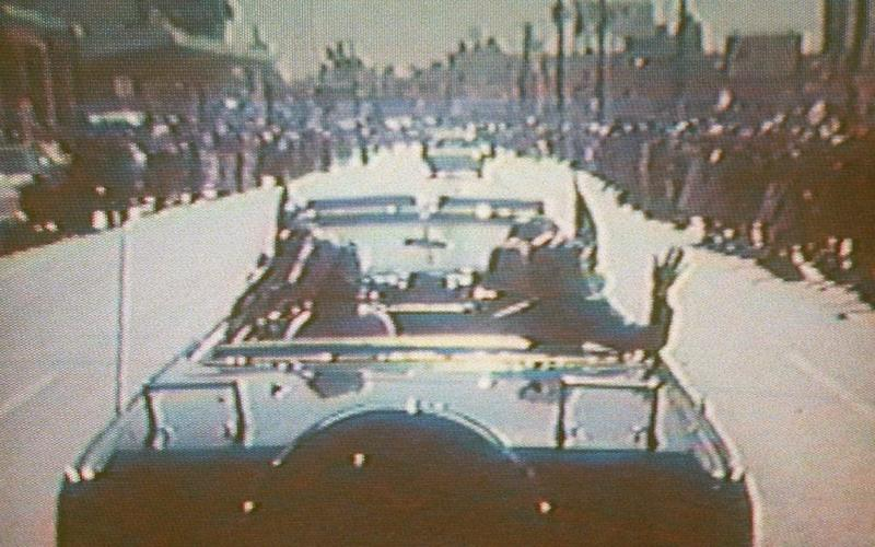 President Kennedy, accompanied by his wife Jacqueline, waves from his limousine during his motorcade in Dallas Nov. 22, 1963 - AP