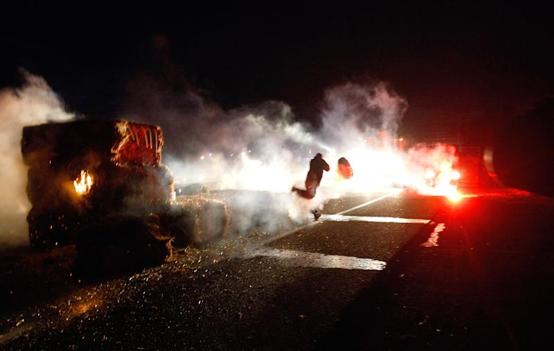 """A farmer throws a tire towards police as farmers block a main road, facing the police, in Arles, southern France,Friday, Nov. 15, 2013. Demonstrators are protesting against the controversial governmental environment """"eco-tax"""". (AP Photo/Claude Paris)"""