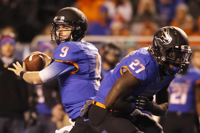 Boise State quarterback Grant Hedrick (9) fakes a handoff to running back Jay Ajayi (27) and then passes during the first half of an NCAA college football game against Wyoming in Boise, Idaho, Saturday, Nov. 16, 2013. (AP Photo/Otto Kitsinger)